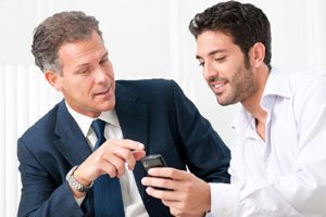 Two businessmen discussing Online Advertising, digital advertising, internet advertising, online ads on their smartphone