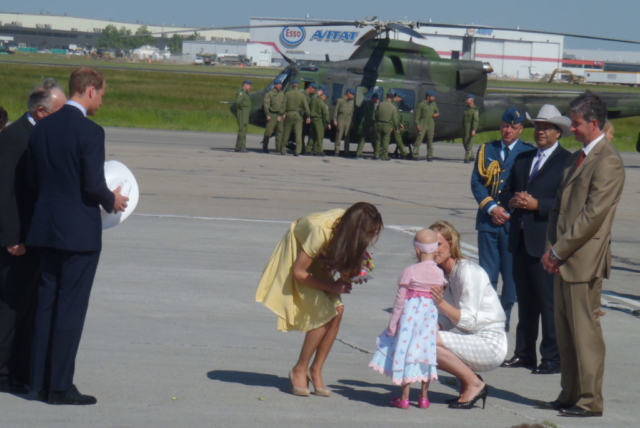kate receiving welcome bouquet from girl at airport
